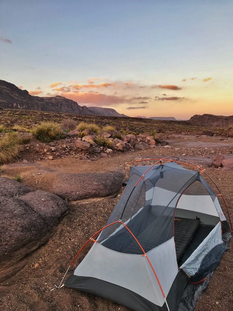 A tent sitting in a dry riverbed and the sun sets.