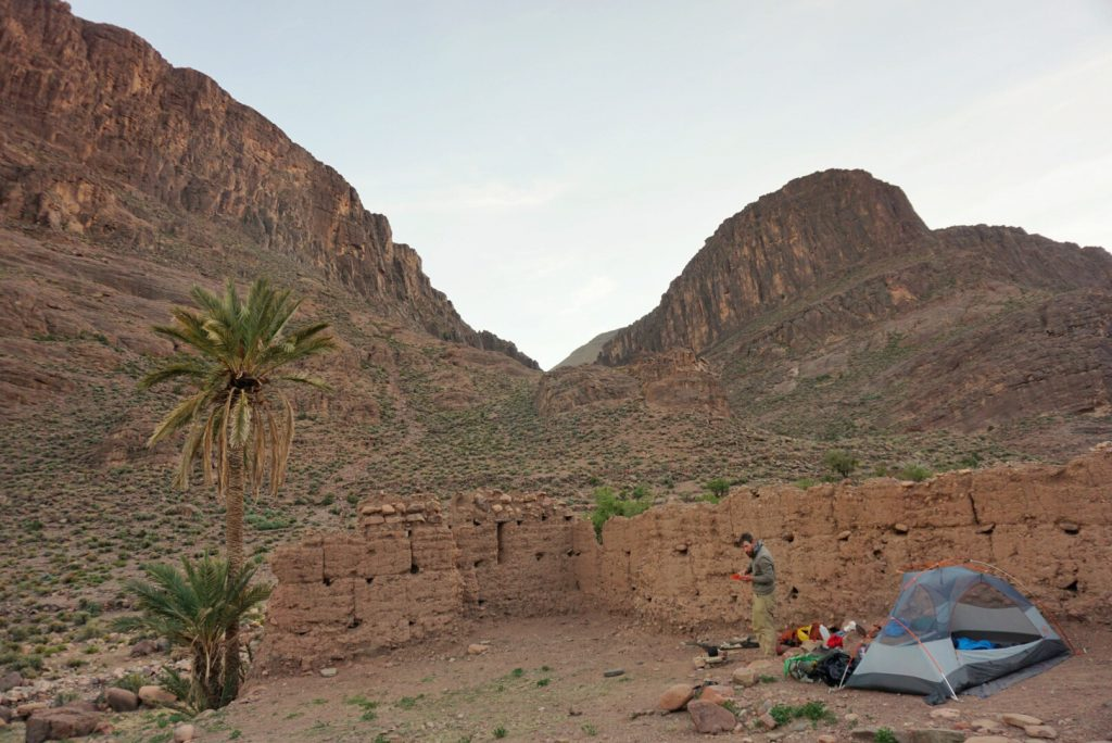 The ruins of a Kasbah with a tent set up inside.
