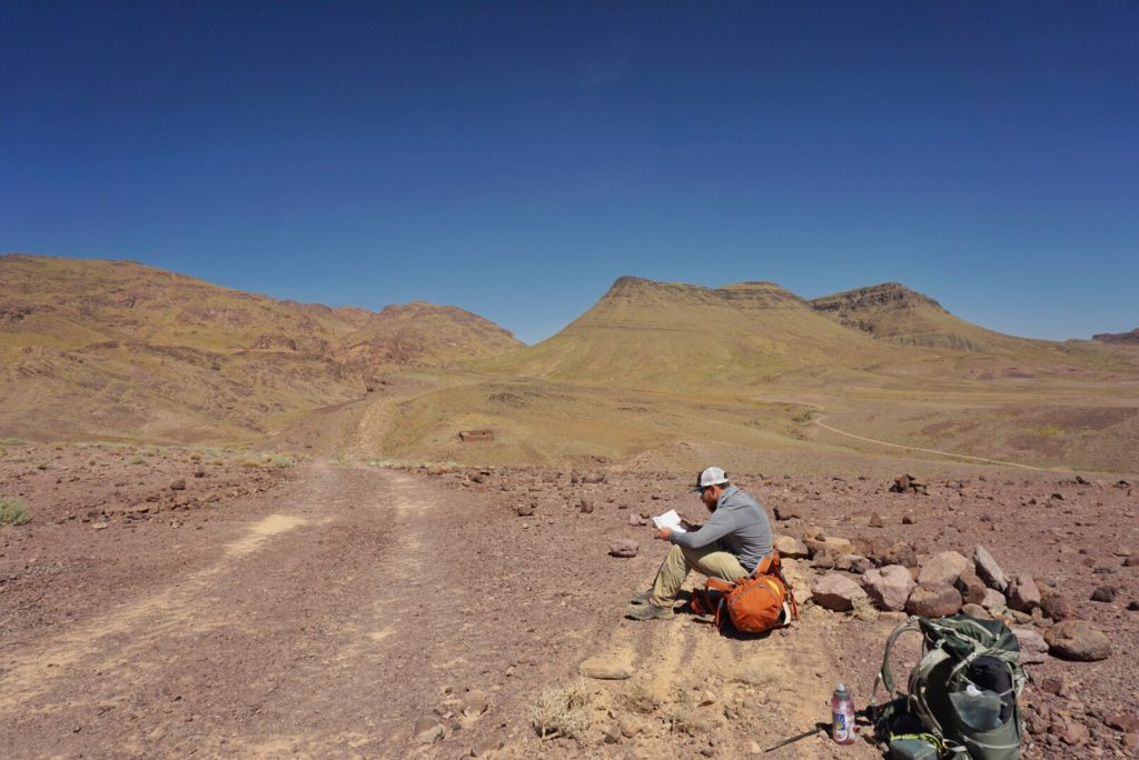 A hiker sits by his backpack by a dirt road.